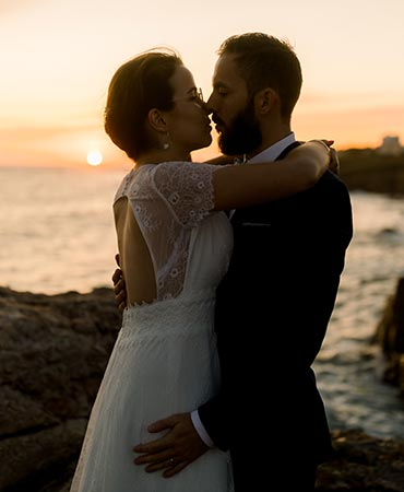Newly wed couple kissing at sunset on the French seaside of Vendee